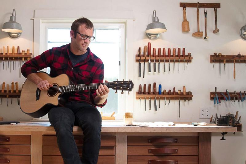 andy power jouant une guitare taylor dans son atelier de lutherie